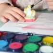 Little girl painting figurine — Stock Photo