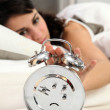 Woman turning off alarm - Stock Photo