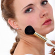 Young woman putting make up on her face — Stock Photo