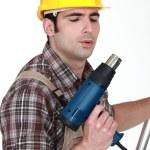 Tradesman blowing on his screw gun — Stock Photo