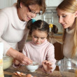 Stock Photo: Little girl preparing cake with her mother and her grandmother