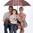 Stock Photo: Young family sheltering under umbrella