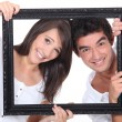 Couple holding empty picture frame — Stock Photo