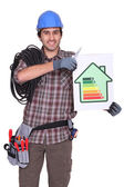 Craftsman holding an energy consumption label — Stock Photo