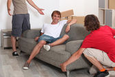 Three young men moving room — Stock Photo