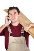 Labourer carrying planks of wood — Stock Photo