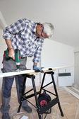 Hombre usando taladro eléctrico de tablón de madera — Foto de Stock