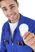 Happy electrician in jumpsuit holding bulb — Stock Photo
