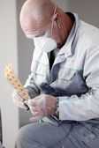 Decorator fitting sandpaper onto an electric sander — Stockfoto