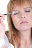 Ginger woman making up eyelids — Stockfoto