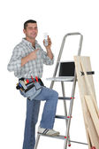 Carpenter posing by step-ladder — Stock Photo
