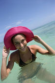Beaming young woman bathing with hands to her sun hat — Stock Photo