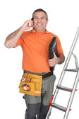 Man on cellphone with ladder and plumbing tools — Stock Photo