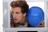 Man with a hard hat and hammer inside a TV set — Stock Photo