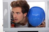 Uomo con un cappello duro e martello all'interno di un televisore — Foto Stock