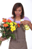 Young woman florist on white background — Stock Photo
