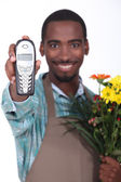 Florist smiling and holding a phone — Stock Photo
