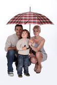 Young family sheltering under an umbrella — Stock Photo