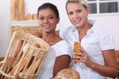 Two young women working in a bakery — Stock Photo