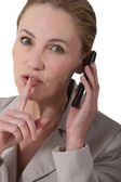 Woman indicating quiet whilst holding a phone — Stock Photo