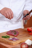 Man putting herbs on a piece of meat — Stock Photo