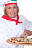 55 years old female pizza cook using a spade and wearing uniform pizza cook — Stock Photo
