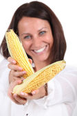 Woman offering two cobs of sweetcorn — Stock Photo