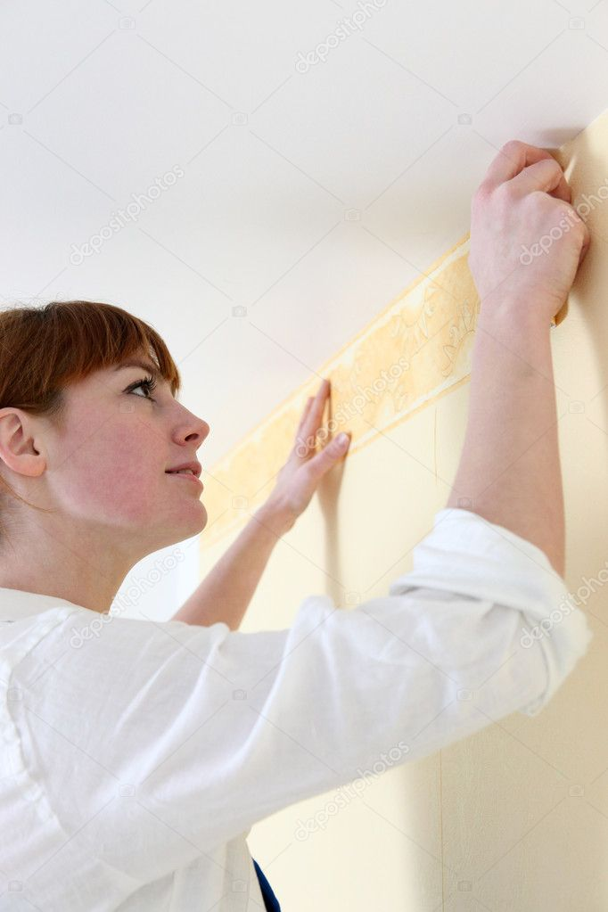 Woman putting up a wallpaper border — Stock Photo #10855316