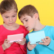 Stock Photo: Children playing with handheld game console