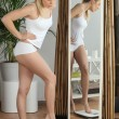 Blond woman weighing herself — Stockfoto