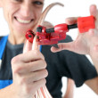 Female plumber cutting copper pipe - Stock Photo
