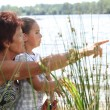 Woman and little girl at a riverside — Stock Photo