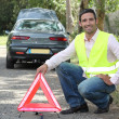 Stock Photo: Man putting out a hazard triangle