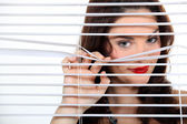 Pretty woman behind blinds spying upon neighbours — Stock Photo
