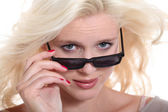 Blonde woman peering over her sunglasses — Stock Photo