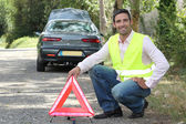 Man putting out a hazard triangle — Stock Photo
