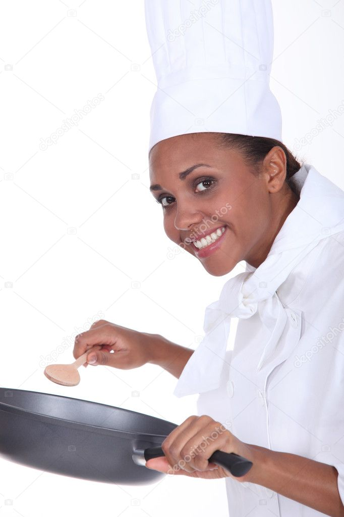 Female chef in uniform with a deep frying pan and wooden spoon — Stock Photo #10860728