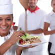 A cook holding a dish, a pizza cook and a waitress dressed in uniform - Stockfoto