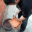 Mason applying cement on a cinderblock - Stock Photo