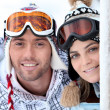 Playful young couple enjoying their skiing holiday — Stock Photo