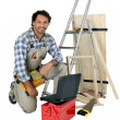 Stock Photo: Tradesman posing with his building materials, tools and laptop