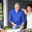 Middle-aged couple cooking outdoors together — Stock Photo #10883364