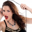 Crazy woman stretching her headphones - Stok fotoraf