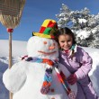 Little girl with snowman - Stock Photo