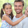 Young family stood in garden — Stock Photo
