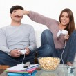 Couple playing video game and eating popcorn — Stock Photo