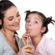 Mother and daughter drinking through straws — Stock Photo