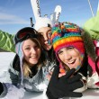 Three friends laying in the snow with ski equipment - Stock Photo