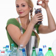 Stock Photo: Womrecycling batteries and plastic bottles