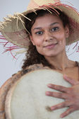 Woman in straw hat holding bongo drum — Stock Photo